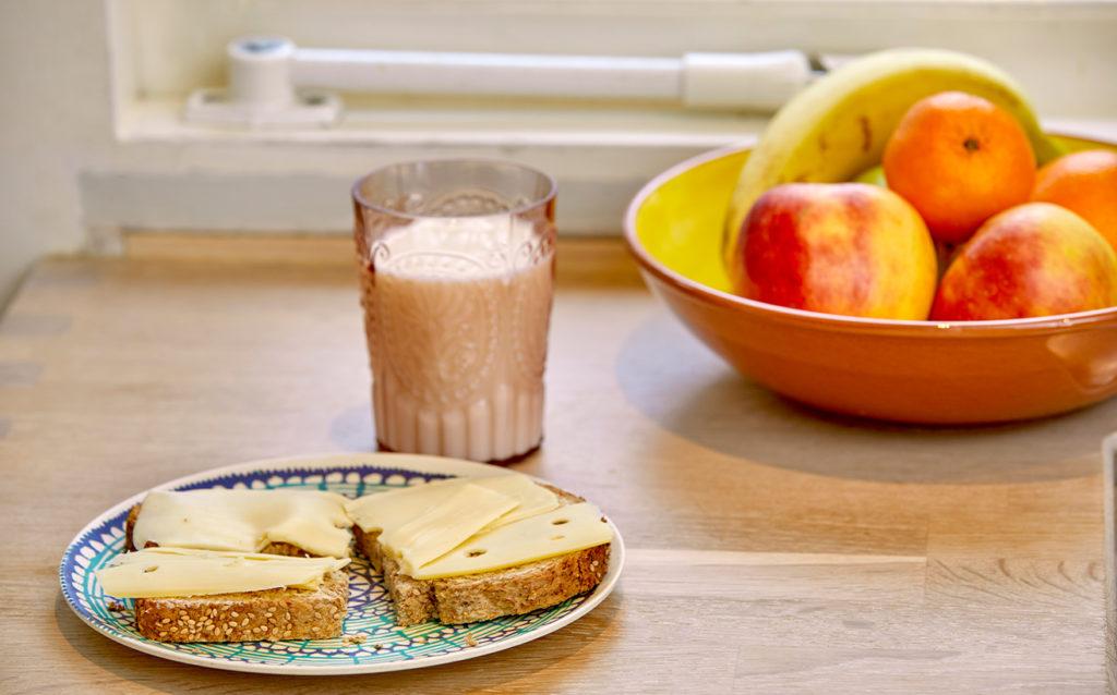 Boterham met kaas, een glas melk en een fruitschaal.